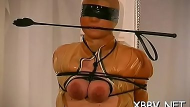 Woman stands with her marangos fastened up in hot bondage scenes